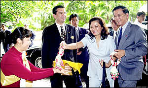 Vietnam's Foreign Minister Nguyen Dy Nien, right, smiles as his wife reaches out for a garland presented by hotel staff in Bangkok