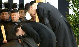 Prime Minister Yoshiro Mori and his wife Chieko bow  before  the main altar