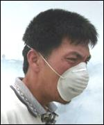 A man has to wear a mask as smoke concentrates from burning forests