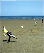 Boy playing football on beach