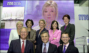 The ITN News Channel team: Carol Barnes, Daljit Dhaliwal, Alison Bell, Leyla Daybelge, Ros Childs, (front row), Andrew Harvey, John Suchet, and Simon Vigar, with Julia Somerville on the screen
