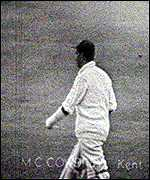 Colin Cowdrey walking to the crease with his left arm in plaster