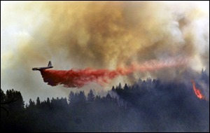 firefighting plane unloads over forest