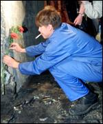 Municipal workers with flowers at Moscow blast scene