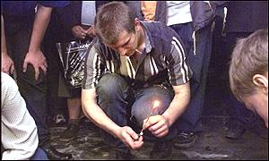 Man lights candle at scene