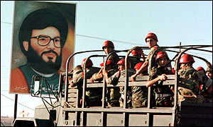 Troops pass by banner showing Hezbollah leader Hassan Nasrallah