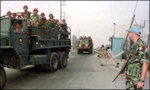 Tank carrying Lebanese troops passes by a UN peace-keeping solider