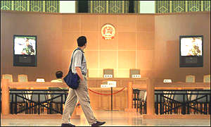 A Chinese journalist walks past a mock Chinese criminal law trial court at a corruption and economic crime exhibition