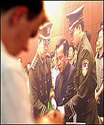 A foreign journalist, standing next to a photo of former chairman of the National Peoples Congress (NPC) Cheng Kejie - the highest ranking Chinese official to be sentenced to death for graft