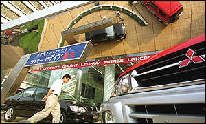 A shopper on the forecourt of Mitsubishi sales centre in Japan