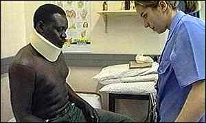James Diop, a Sudanese refugee, is assisted by a nurse following a racist attack