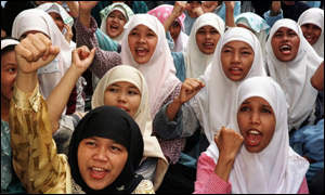 image: [ Female students wearing traditional Muslim dress block traffic during a protest in Jakarta ]