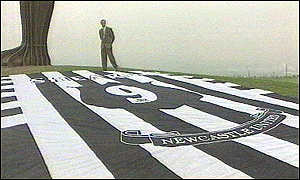 image: [ Around 25 Newcastle United fans put the 29ft x 17ft shirt on the Angel ]