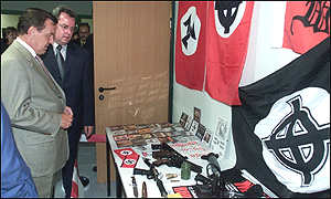 Schroeder inspects a collection of seized neo-Nazi weapons and propaganda materials in eastern Germany