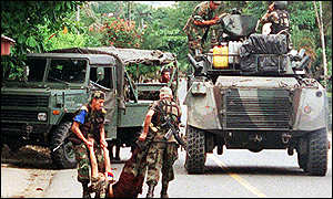 Colombian army carry body of a suspected guerrilla