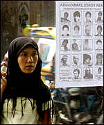 Woman looks at wanted poster of Abu Sayyaf kidnappers