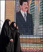 Iraqi women pass by portrait of Saddam