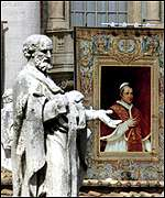 A tapestry bearing the likeness of Pope Pius IX hangs from St Peters basilica
