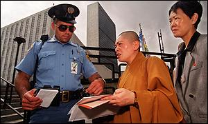Policeman checks a Buddhist monk outside UN headquarters