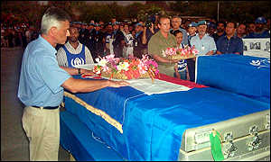 Sergio Vieira de Mello puts flowers on a coffin