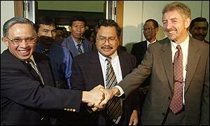Bank Indonesia acting governor Anwar Nasution (left) shakes hands with IMF representative John Dodsworth (right)
