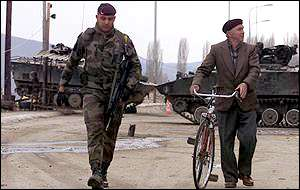 Soldier escorting Mitrovica man