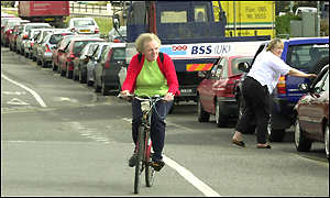 A cyclist passes a queue of cars in Nottingham