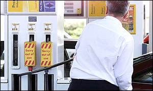 Man fills up car at petrol station where some pumps already closed