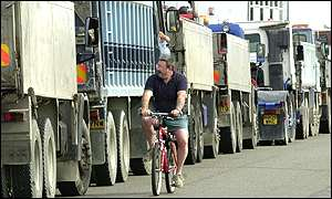 UK Cyclist passing queue of lorries