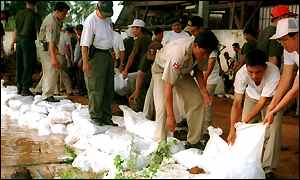Cambodian police officers pile up sandbags just east of Phnom Penh