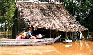 A farming family prepares to leave their flooded house in Hong Ngu district