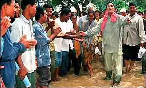 Cambodian Prime Minister Hun Sen (R) greets flood victims