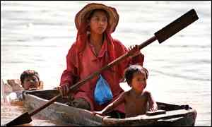 A Cambodian woman paddles a canoe along the Mekong