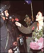 Woman anti-government protester gives a soldier a rose