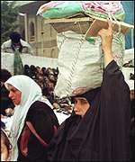 Woman in Baghdad carrying a bagful of UN food rations