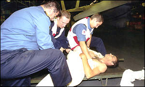 A medical team from Britain's Royal Navy Aircraft Carrier HMS Invincible administer first aid