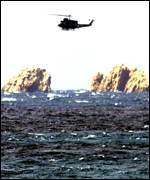 A resuce helicopter searches the rocks near where the ferry sank