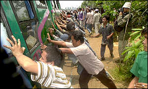 Anti-Suharto protesters push over a bus carrying Suharto supporters