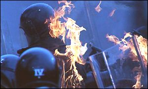 Riot police are hit by a petrol bomb in Northern Ireland