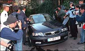 Reporters try to get a picture of Dominique Strauss-Kahn leaving his home