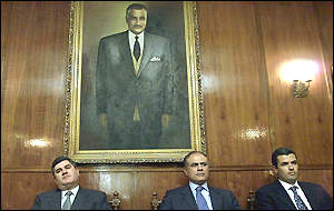 Nasser's sons sit underneath a portrait of their late father
