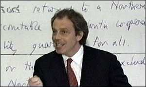 image: [ Tony Blair in front of his handwritten pledges to the people of Northern Ireland ]