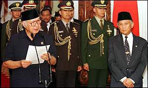 image: [ Flanked by military leaders and his successor B.J. Habibie, President Suharto makes his fateful announcement ]