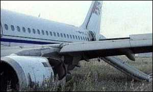 image: [ The plane skidded to a stop on grass ]