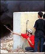 Palestinian youths use a slingshot to fire stones at Israeli police