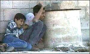 Muhammad and his father cower behind a concrete wall