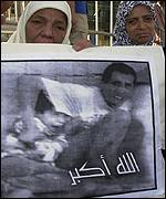 Women hold picture of death of Muhammad al-Durrah and caption Allahu Akbar