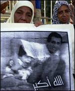 Palestinian women in Lebanon hold up a portrait of Mohammad Al-Durra