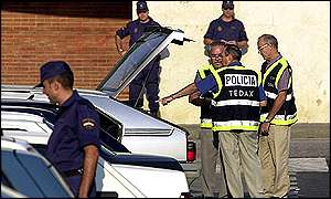 Bomb disposal officers examine a car in Seville