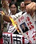 Protesters burn picture of Mr Tung